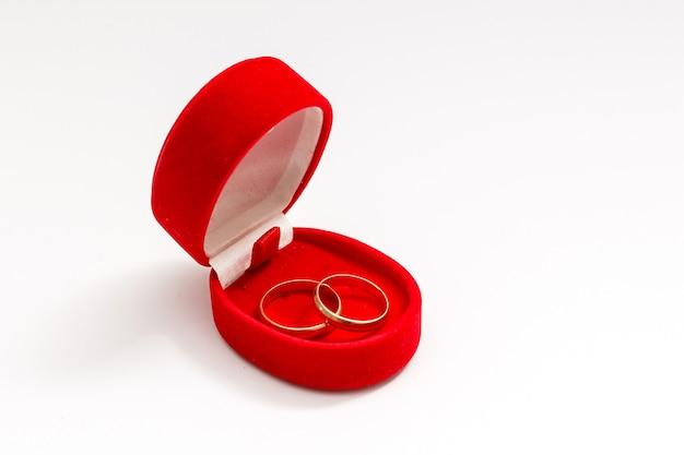 Twee trouwringen in mooie rode doos geïsoleerd op een witte achtergrond