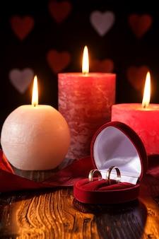 Twee trouwringen in rode geschenkdoos met drie wax vlam kaarslicht met lint in donker romantisch licht op harten
