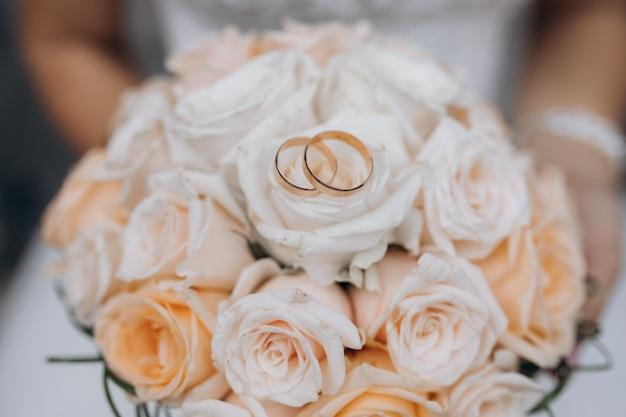 Twee trouwringen liggen op een bruidsboeket