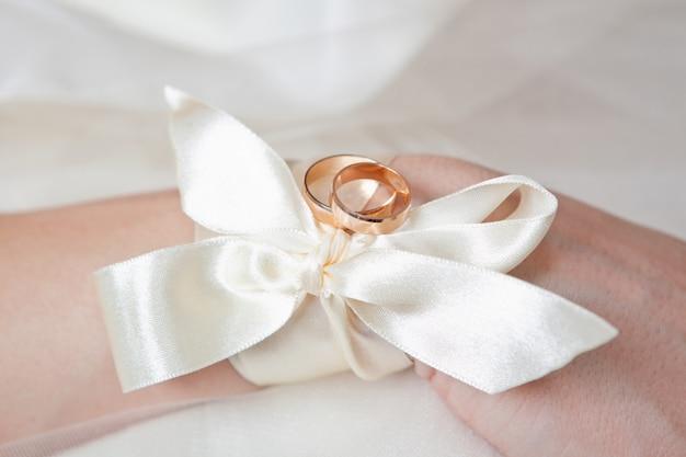 Twee trouwringen met witte bloem liggen aan de vrouwenhand