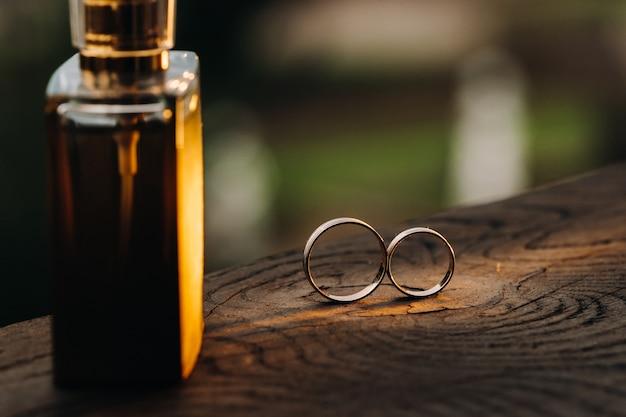 Twee trouwringen op een houten sokkel voor een gouden ring van een liefdevol bruidspaar