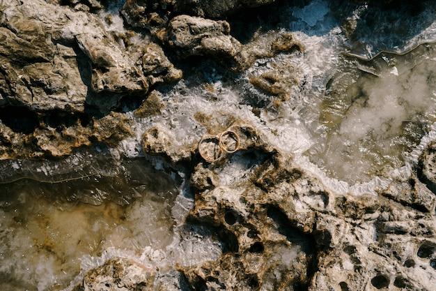Twee trouwringen op een stenen structuur in zeezout