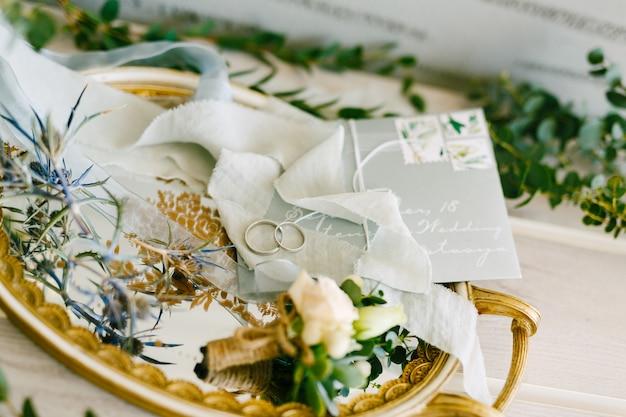 Twee trouwringen voor de bruid en bruidegom en op een dienblad met gouden patronen corsages lint