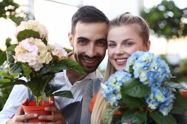 Twee tuinlieden die het portret van de hydrangea hortensiabloem tonen