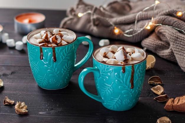 Twee turquoise keramische kopjes warme chocolademelk met marshmallows op een donkere houten tafel