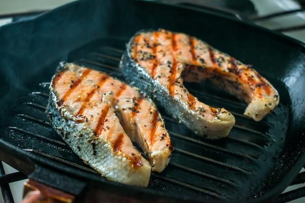Twee twee geroosterde zalmlapjes vlees met kruiden en specerijen op een grillpan