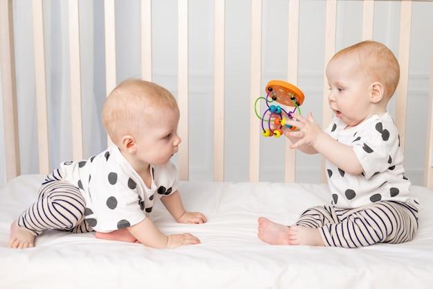 Twee tweeling baby's van 8 maanden spelen in de wieg, vroege ontwikkeling van kinderen tot een jaar, het concept van de relatie van kinderen van broer en zus, een plek voor tekst