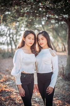 Twee tweeling tienermeisjes jonge vrouw die en pret lachen hebben dichtbij de tuin in zonsondergangtijd