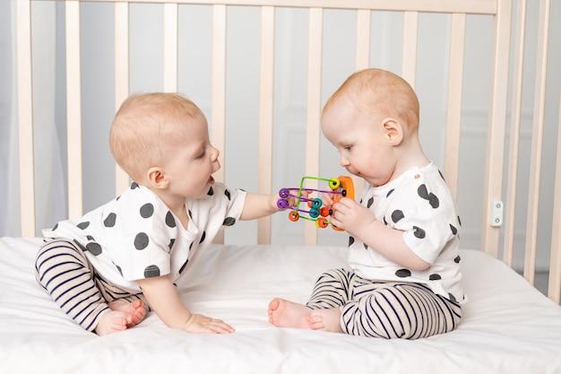 Twee tweelingbaby's van 8 maanden oud spelen in de wieg, vroege ontwikkeling van kinderen tot een jaar, het concept van de relatie van kinderen van broer en zus, het kind neemt het speelgoed van de ander over.