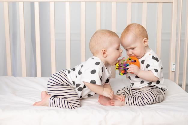 Twee tweelingbaby's van 8 maanden spelen in de wieg, vroege ontwikkeling van kinderen tot een jaar, het concept van de relatie van kinderen van broer en zus, het kind neemt het speelgoed van de andere