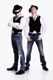 Twee tweelingbroers in gangsterstijl poseren. hoeden, vesten, witte overhemden. witte achtergrond.