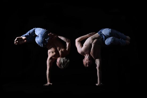 Twee tweelingbroers in spijkerbroek met een naakte torso voeren acrobatische elementen uit, zwarte achtergrond