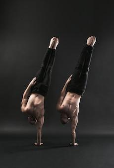 Twee tweelingbroers in zwarte jeans met een naakte torso voeren acrobatische elementen uit, zwarte achtergrond