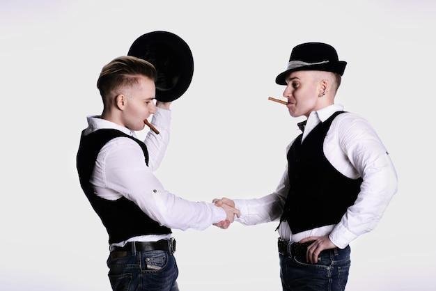Twee tweelingbroers met hoeden en sigaren in hun mond schudden elkaar de hand. wit overhemd en vest. witte achtergrond