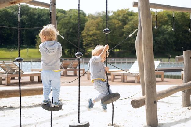 Twee tweelingbroers van twee jongens spelen op een kinderspeelplaats op een zonnige herfstdag
