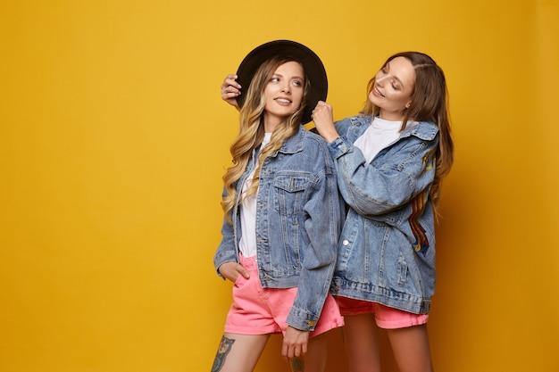 Twee tweelingen die jeansjasjes dragen