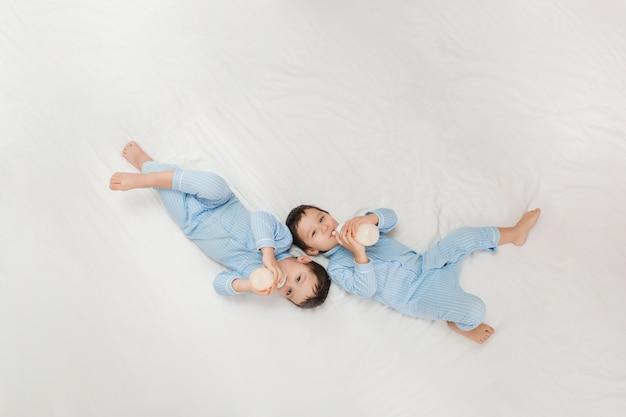 Twee tweelingjongens in pyjama's liggen op het bed met consumptiemelk uit flessen. uitzicht van boven. concept van huwelijk en vriendschap. concept van babyvoeding. ruimte voor tekst