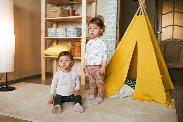 Twee tweelingmeisjes staan op de grond in een kamer naast een gele hut. spelletjes voor kinderen