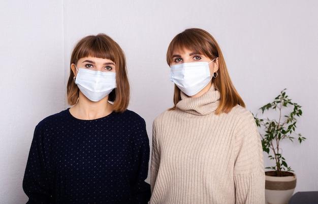 Twee tweelingzusjes maskeerden vrouwen op het werk. social distancing. nieuwe realiteit. levensconcept tijdens de coronavirus-pandemie.