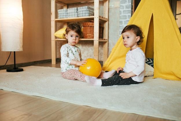 Twee tweelingzusjes zitten tegenover elkaar op de grond en spelen met een gele bal. gele wigwam
