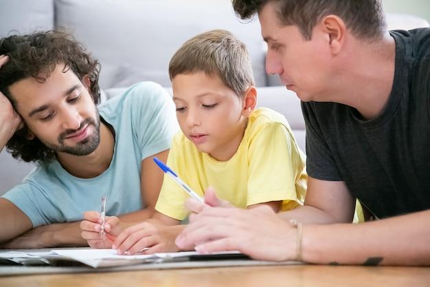 Twee vaders helpen gefocuste jongen met schoolhuistaak, thuis op de vloer liggen, schrijven of tekenen in papieren. familie en homo-ouders concept