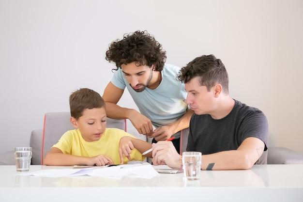 Twee vaders helpen gerichte jongen met school huistaak, zittend aan tafel met papieren, leerboek samen lezen, wijzende vinger op pagina. familie- en ouderschap concept