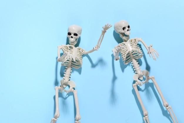 Twee valse skeletten op helder blauw. halloween-decoratie, eng thema