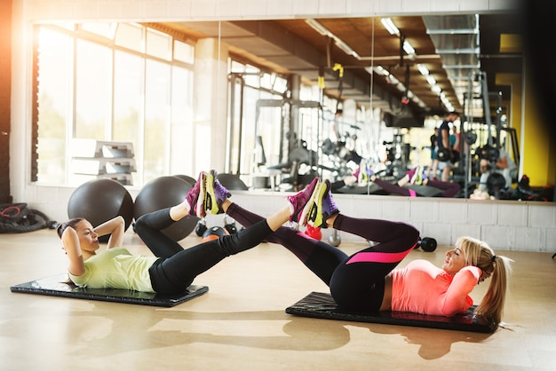 Twee vastberaden jonge meisjes die crunches doen met benen in de lucht.