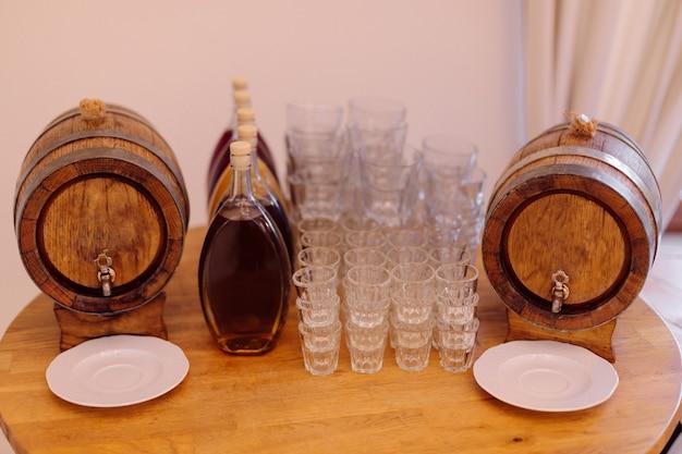 Twee vaten lokale traditionele alcoholische dranken en verschillende glazen glazen houten tafel