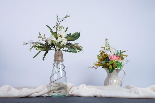 Twee vazen met kleurrijke bloemen op donkere tafel.