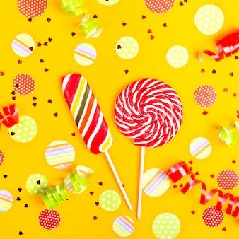 Twee veelkleurige snoepjes onder papieren cirkels van confetti, glitter en feestelijke linten