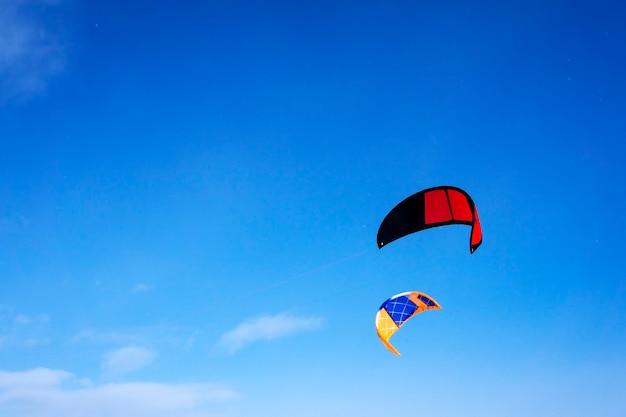 Twee veelkleurige sportvliegers voor vliegeren of snowkiten op een achtergrond van blauwe lucht met wolken