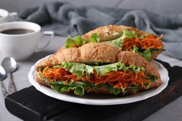 Twee vegetarische croissants-sandwiches met sla, wortelen, komkommers en twee kopjes koffie op een lichtgrijze betonnen achtergrond