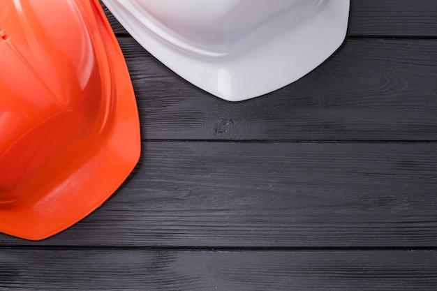 Twee veiligheidshelmen op zwarte houten tafel. witte en oranje constructorhelmen en kopieerruimte.