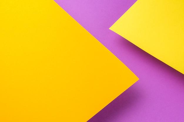 Twee vellen geel en oranje papier vliegen boven de paarse achtergrond. de bladen werpen een schaduw.
