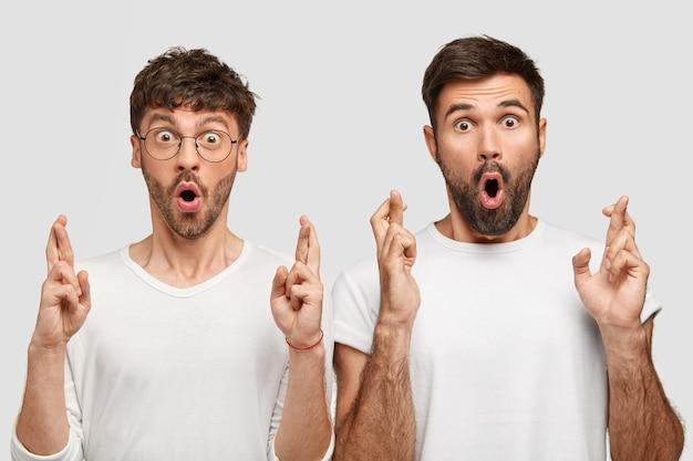 Twee verbaasde man student kruisen vingers als bidden voor geluk, voelen geschokt terwijl resultaten van examen anticiperen, opent mond wijd