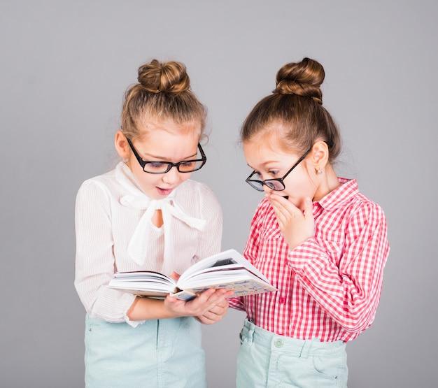 Twee verbaasde meisjes in glazen die boek lezen
