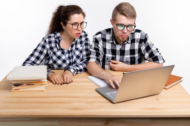 Twee verbaasde studenten in geruite overhemden die aan tafel zitten.