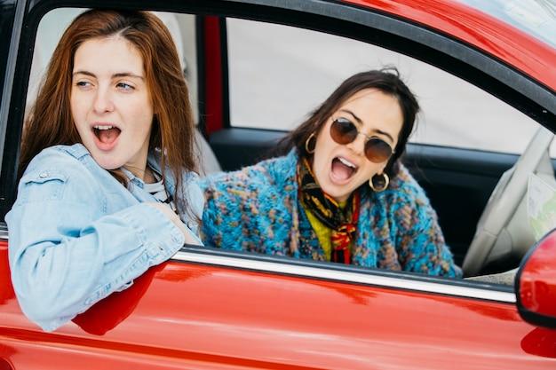 Twee verbaasde vrouwen die uit van autoraam kijken