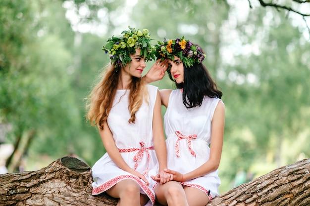 Twee verbazende etnische volksstijlmeisjes met kroon van bloemen die tijd samen in weekend zonnige dag doorbrengen bij aard in de zomer. vrolijke vrouwelijke paarvrienden die elkaar handen houden.