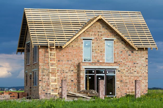 Twee verdiepingen tellende woonhuis met kunststof ramen, brede deur en houten frame voor dak in aanbouw. hoge houten ladder op bakstenen muren en bakstenen kolommen voor hek op donker blauwe hemel