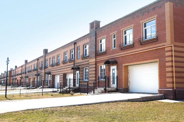 Twee verdiepingen woongebouw met aparte ingangen voor de appartementen en individuele garages. townhouse. vergast. gebouwd van rode, gele en bruine bakstenen. kopieer ruimte.