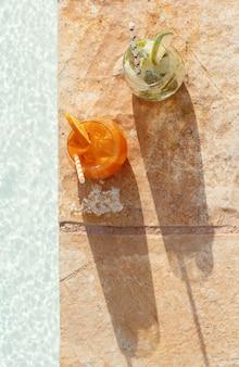Twee verfrissende cocktails bij het bovenaanzicht van een zwembad