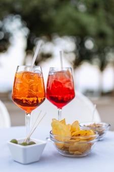 Twee verfrissende italiaanse cocktails met hapjes op tafel (verticale foto)