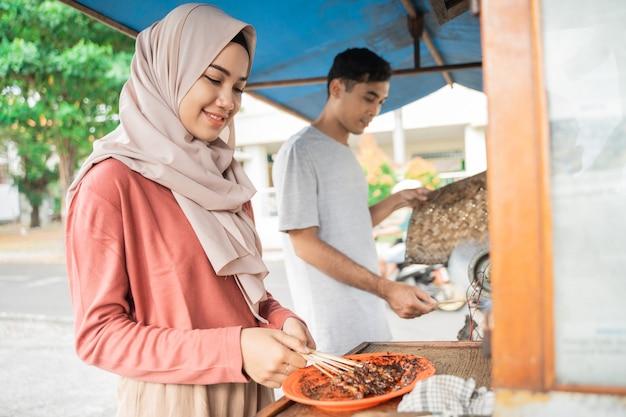 Twee verkopers die voedsel bereiden op hun eetkraam en traditionele kipsaté verkopen