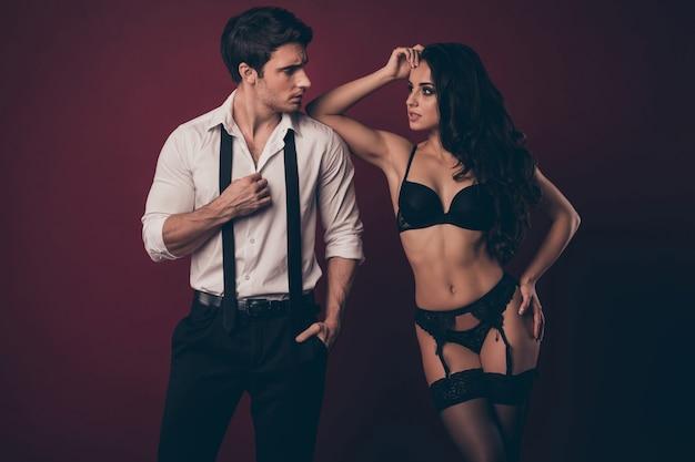 Twee verleidelijke mensen man vrouw poseren. vrouw leunt met haar elleboog op zijn schouder