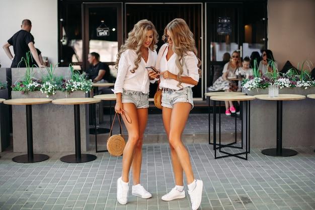 Twee verleidelijke vrouwen die samen tijd doorbrengen, gebruikend bij telefoongesprek