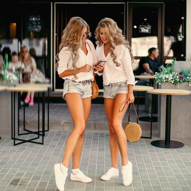 Twee verleidelijke vrouwen die samen tijd doorbrengen, gebruikend smartphone
