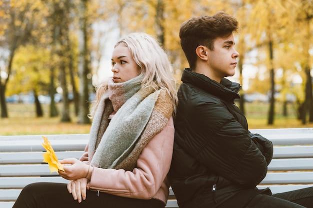 Twee verliefde tieners in ruzie. brunette jongen en blond meisje zitten
