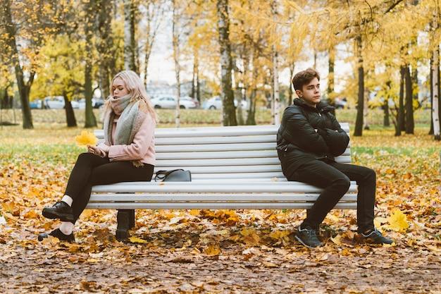 Twee verliefde tieners in ruzie. een donkerbruine jongen en een blond meisje zijn sittingept